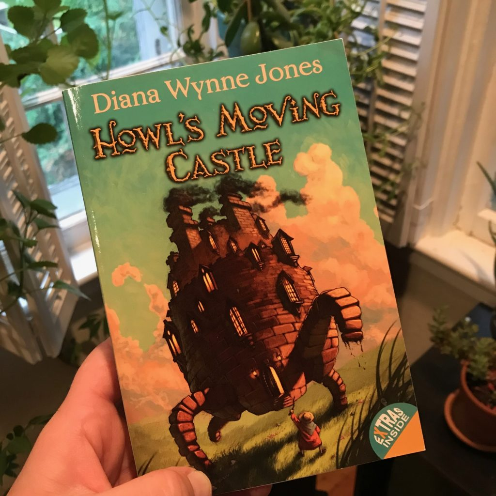 "Cover of the book ""Howl's Moving Castle"" with a brick castle with four legs walking across the grass, and a figure seen from behind holding up a stick toward it."